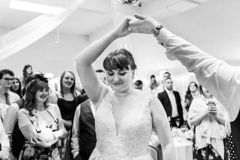 groom spinning his bride on the dance floor