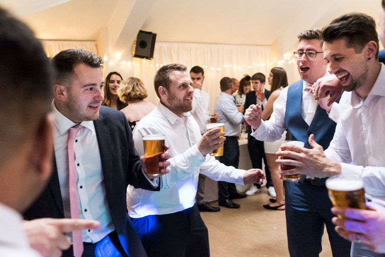 groom's friends dancing with their pints