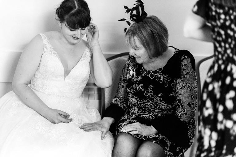mother of the bride admiring her daughter's wedding dress