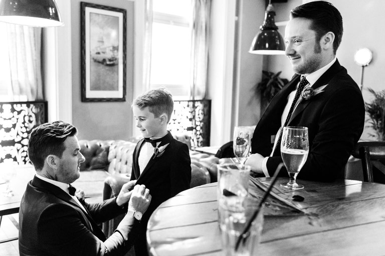 groom helping his son with tuxedo