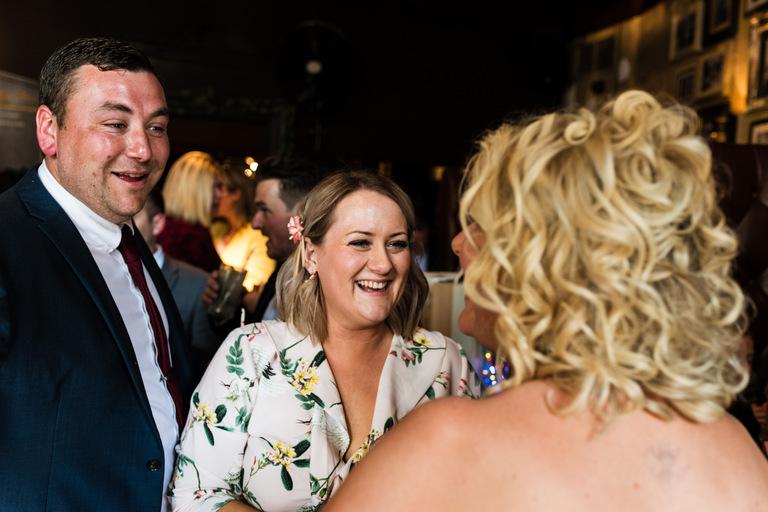 smiling guests greet bride