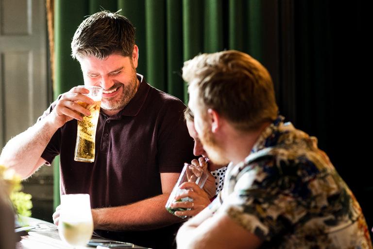 friends share a joke over a drink