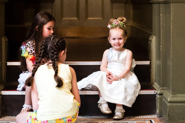 cute little flower girl sat on a step