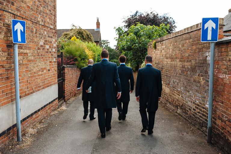 groomsmen walking down a one way street