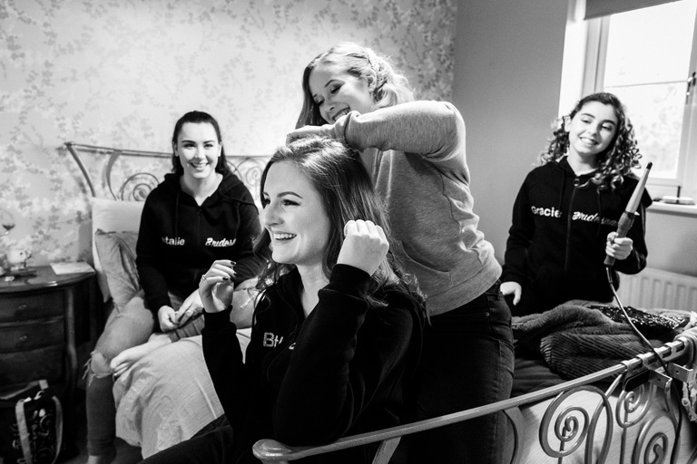 bride helping bridesmaid with her hair