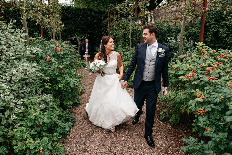bride and groom walking through a garden