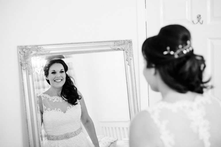 smiling bride looking in the mirror
