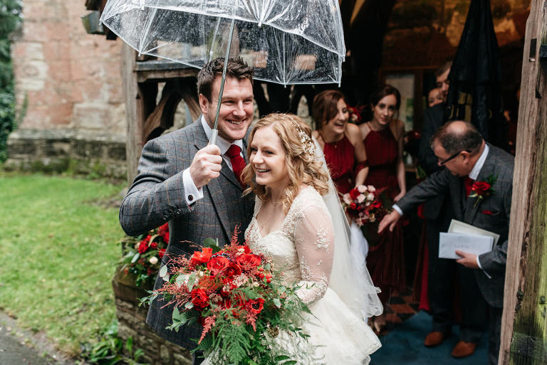 bride and groom under umbrella in the rain